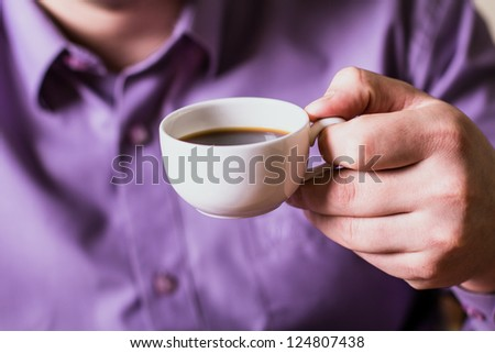 A man holding a cup of coffee - stock photo