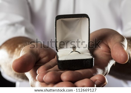 A Man holding a diamond ring in a gesture of giving.