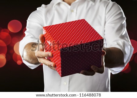 A Man holding a gift box in a gesture of giving.
