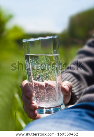 A man holding a glass of clean water