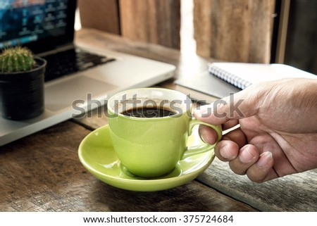 A Man Holding a Green cup of Coffee with note book on wood table. #375724684