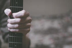 A man holding a guitar neck, close-up, space for text