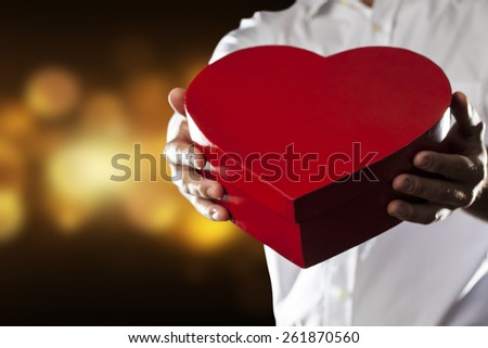 A Man holding a heart gift box in a gesture of giving in a yellow lights background