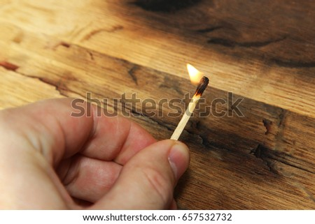 A man holding a lit match. This image also contains a wooden background and can be used to represent fire starting or arson.  Stock photo ©