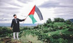 a man holding a Palestinian flag for peace and campaign to stop war