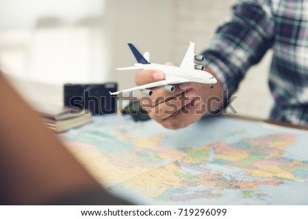 A man holding a plane model over a world map while planning holiday travel aboard for him and his partner to their dream destinations #719296099