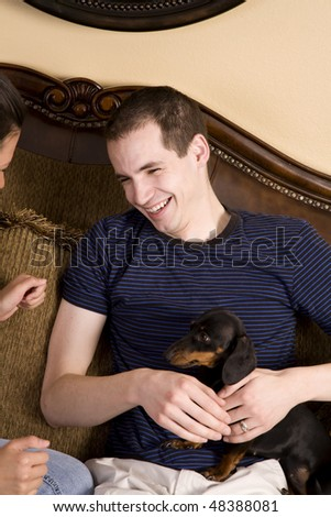 A man holding a puppy on his lap on the couch while he is laughing with his wife.