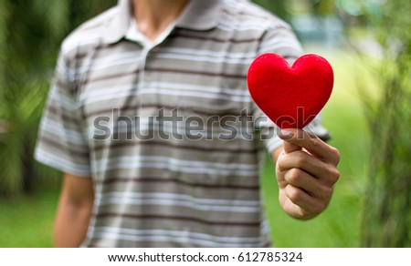 a man holding a red heart #612785324