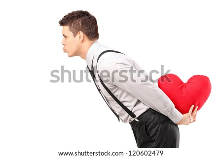 A man holding a red heart shape object and giving kisses isolated on white background