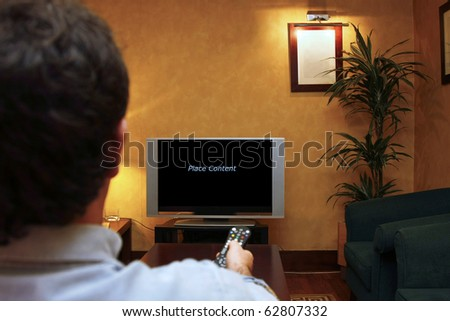 A man holding a remote control while watching TV. Empty space to place content.
