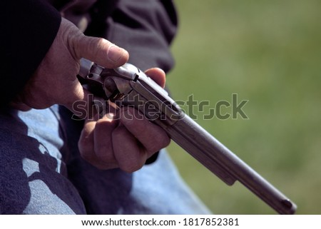 Photo of  A man holding a replica of a vintage firearm.