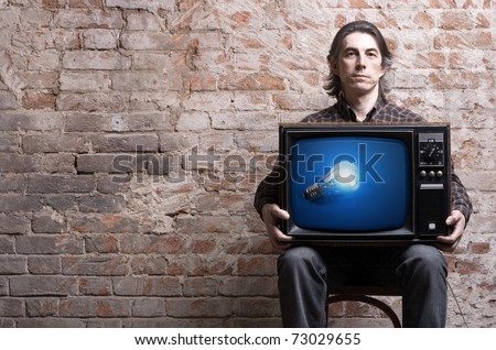 A man holding a retro TV with a picture of a glowing light bulb .