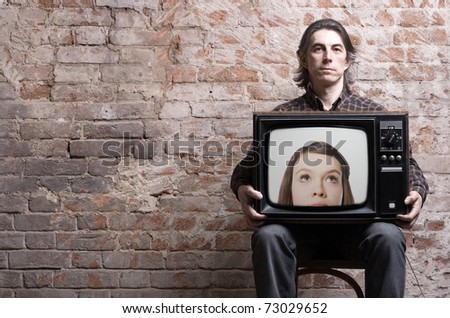 A man holding a retro TV with the head of a girl looking at him .