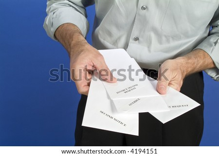 A man holding a several white envelopes with past due notices on them.