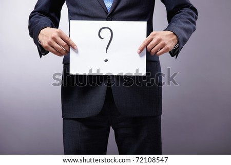 A man holding a sign with a question mark