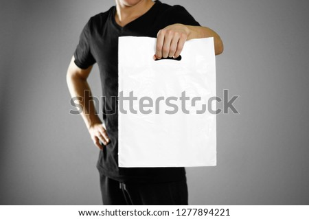 A man holding a white plastic bag. Close up. Isolated on grey background.