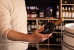 A man holding  a wine bottle in a liquor wine shop. Choosing the right wine from all the variations of wine bottles on the shelves in the bokeh background.