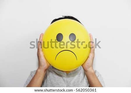 A man holding a yellow balloon with sad face emotion instead of head