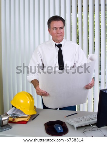 A man holding building plans or blueprints standing in front of a desk with a hardhat and computer on it.