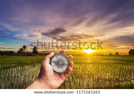 A man holding compass on hand at field and sunset for navigation guide.