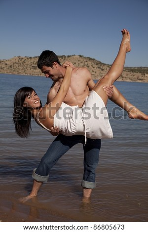A man holding his girl up in the air dipping her while he stands in the water.