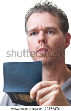 A man holding his passport in front of himself, open, and looking up, isolated on white. - stock photo