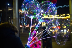 A man holding illuminating balloons with led garland in the street during the night.