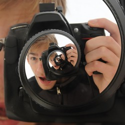A man holding up a DSLR camera taking a never ending picture. The name for this effect is called the droste effect.