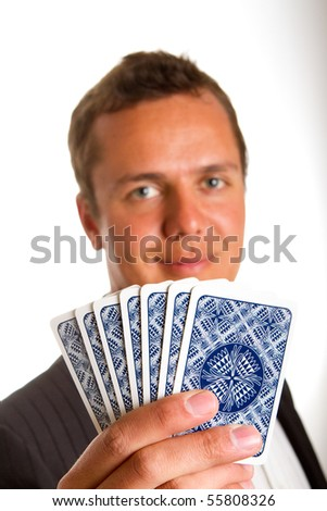A man holding up a few playing cards