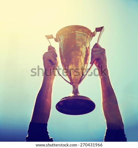 a man holding up a gold trophy cup as a winner in a competition toned with a retro vintage instagram filter effect app or action (backlit with the sun) #270431966