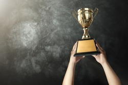 a man holding up a gold trophy cup with grunge wall background copy space ready for your trophy design.
