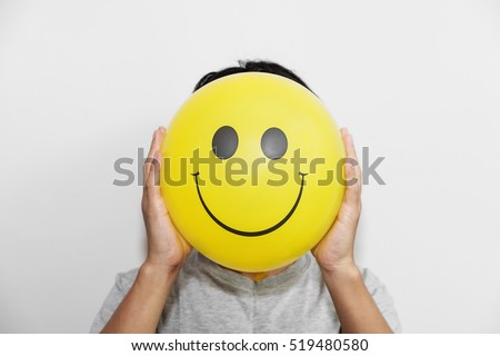 A man holding yellow balloon with smile face emotion instead of head. Positive Thinking concepts. hiding some bad feeling just keep smiling