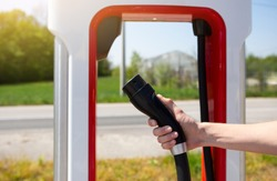 A man holds a charger plug for an electric car