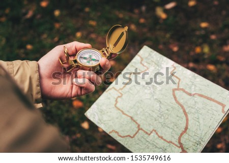 A man holds a compass and a paper map in his hand and is guided by the area, autumn forest, walk,hiking