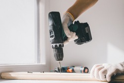 A man holds a cordless screwdriver in his hand and wraps the screw in a Board. Carpenter working with an electric screwdriver on the work bench