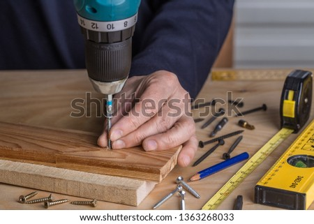 A man holds a cordless screwdriver in his hand and wraps the screw in a pine Board. Carpenter working with an electric screwdriver on the work bench