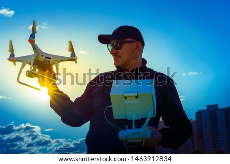 A man holds a drone and remote control. Hobby launching drones. Quadcopter for photo and video. Unmanned aerial vehicles.
