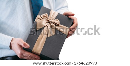 A man holds a gift in his hands with a brown ribbon. Guy on a white background in a light shirt with a tie. Black gift box in hands. Place for inscription.