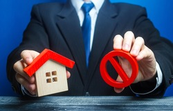 A man holds a house and the red prohibition symbol NO. Bank refuses to provide a mortgage loan. Housing problems. Confiscation pledged property. Prohibition of operation. Denial of insurance payment.