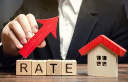 A man holds a red arrow up above the word Rate and a wooden house. The concept of raising interest rates on mortgages. The increase in property tax rates. Real estate capitalization. Insurance.