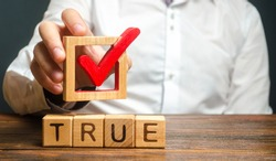 A man holds a red check mark over word True. Confirm the veracity and truth. Fight against fake news hostile propaganda. Confirmation facts, refutation of rumors. Debunking Myths and Misconceptions