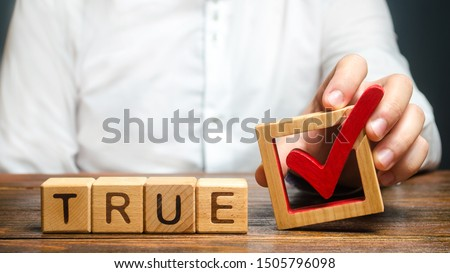 A man holds a red check mark over word True. Confirm the veracity and truth. Fight against fake news hostile propaganda. Confirmation facts, refutation of rumors. Debunking Myths and Misconceptions #1505796098