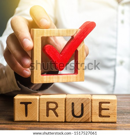 A man holds a red check mark over word True. Confirm the veracity and truth. Fight against fake news hostile propaganda. Confirmation facts, refutation of rumors. Debunking Myths and Misconceptions #1517527061