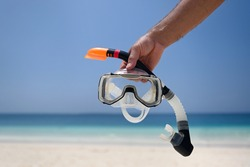 A man holds a snorkel mask in his hand against a clear blue sky and turquoise ocean. Diving mask in a man's hand. Photo of a mask and snorkel for swimming in a pool or sea with a central composition