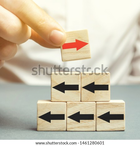 A man holds a wooden block with red arrow facing the opposite direction black arrows. Individual opinion. Stand out from the crowd. Uniqueness. Divergent views. Different concepts to other people.