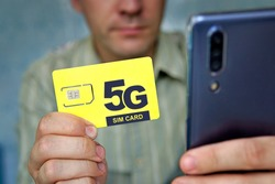 A man holds a yellow SIM card with the inscription 5G and a mobile phone in his hand. Replacing the SIM card and switching to high-speed Internet.