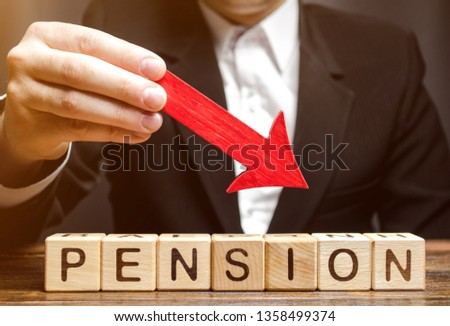 A man holds an arrow down over wooden blocks with the word Pension. Fall / reduction pension payments. Retirement. Financing retirees. Reduction of the pension fund. The low size of pensions. #1358499374