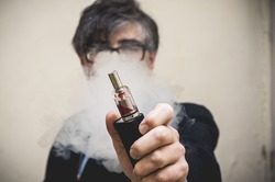 A man holds an electronic cigarette (e-cig) up for the camera while exhaling a cloud of vapor.
