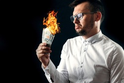 A man holds burning money in his hands, burning US dollars. The concept of inflation, a decrease in the purchase of foreign currency, and devolution.