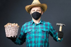 A man holds in his hands a basket with walnuts and a hammer. Farmer with a protective mask on his face. There is a straw hat on his head. Shot on a gray background.